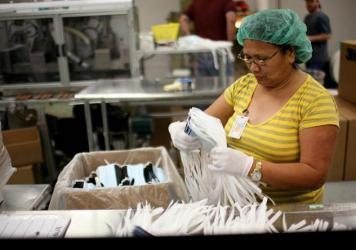 A Prestige Ameritech employee inspects disposable surgical masks in 2009 at the company's Texas factory. The company is one of the last domestic manufacturers of medical face masks.