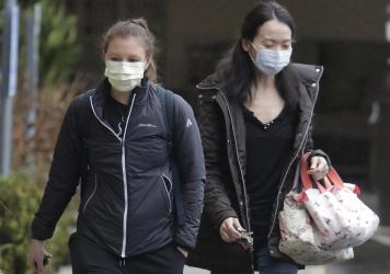 Two women wearing masks walk away from the Life Care Center in Kirkland, Wash., near Seattle. An outbreak of the coronavirus is cited as the cause for the deaths of at least two residents at the center.
