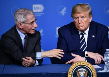 President Trump listens to Anthony Fauci, director of the NIH National Institute of Allergy and Infectious Diseases, after a tour earlier this week.
