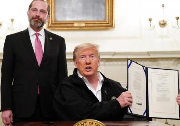 President Trump holds up the $8 billion coronavirus emergency funding bill after signing it at the White House as Health Secretary Alex Azar looks on.