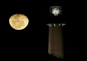 The moon, in its waning gibbous state, rises near the Jupiter Lighthouse in 2013, in Jupiter, Fla. The 108-feet tall, brick structure was first lit in 1860. The lighthouse sits atop a Native American archaeological site, which is at risk from the rising