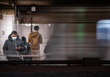 A commuter wearing a medical mask waits for a train Thursday at Grand Central station in New York City. Several dozen cases have been confirmed in the state, and the East Coast as a whole saw its first two confirmed deaths related to COVID-19, in Florida