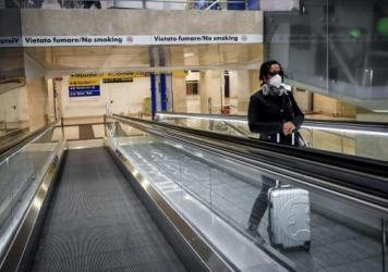 A woman wearing a medical mask rides an escalator at Milan Central train station on Sunday after Italy's government locked down much of the country in an effort to stanch the spread of the coronavirus.