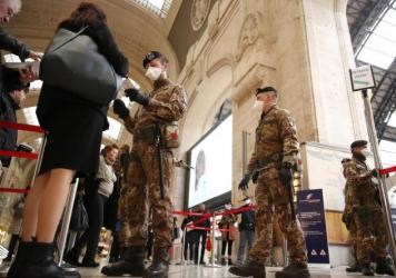 """Police officers and soldiers check passengers leaving from the main train station in Milan, Italy. The government declared on Monday that the whole country is a """"red zone."""""""