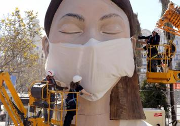 The World Health Organization called the COVID-19 viral disease a pandemic Wednesday. Here, workers in Spain place a medical mask on a figure that was to be part of the Fallas festival in Valencia. The festival has been canceled over the coronavirus outb