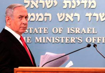 Prime Minister Benjamin Netanyahu approaches the podium to give a speech from his Jerusalem office on Saturday, saying Israel's restaurants and places of entertainment will be closed to stop the spread of the coronavirus. He also encouraged people not to