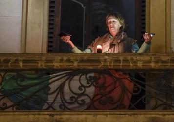 A woman holds lights on her balcony during a flash mob launched throughout Italy on March 15 to bring people together. The Italian government imposed unprecedented restrictions to halt the spread of COVID-19 coronavirus outbreak, among other measures peo