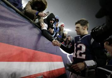 Tom Brady shakes hands with a fan as he leaves the field in Foxborough, Mass., after losing a playoff football game to the Tennessee Titans earlier this year. As it turns out, that was likely the final game the quarterback would play in a New England Pat
