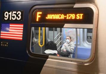 A woman with a face mask rides on the subway on March 17, 2020, in the Brooklyn Borough of New York City. Advocates in the city are reaching out to immigrant communities which face challenges due to the coronavirus epidemic.