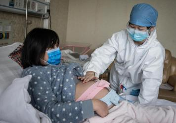 A nurse examines a pregnant woman in a private obstetric hospital in Wuhan, China, in February. Research from China suggests pregnancy does make women more vulnerable to the coronavirus.