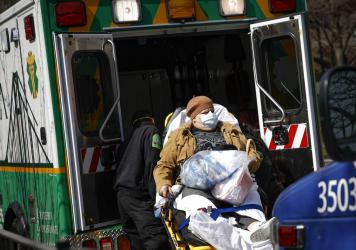 Medical workers load a patient wearing a protective mask into the back of an ambulance Wednesday outside a hospital in Brooklyn. New York has seen a spike in coronavirus cases, and officials are preparing for an influx at medical centers throughout the s