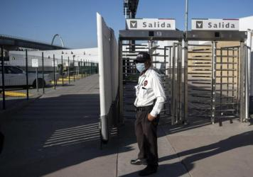 A security guard stands at the El Chapparal Port of Entry on the U.S.-Mexico Border in Tijuana, Baja California state, Mexico, late last month. The two countries are said to be working out a deal to close their border to non-essential crossings.
