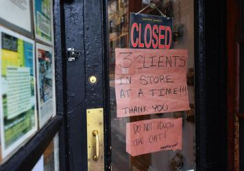 """A butcher shop in the Brooklyn borough of New York shows a """"Closed"""" sign, limiting customers to three at a time. Gov. Andrew Cuomo is ordering all nonessential businesses to close, in an escalation of the state's attempts to contain the COVID-19 pandemic"""