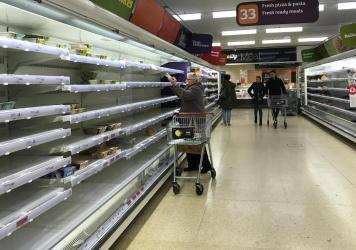 An elderly woman reaches up to a near empty shelf in a supermarket in London on Thursday. The coronavirus outbreak has led to panic shopping in the United Kingdom as elsewhere.