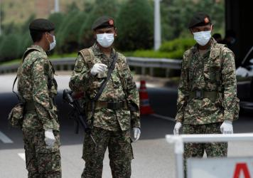 Soldiers in face masks maintain a checkpoint in Putrajaya, Malaysia on Sunday. Malaysian government issued a movement order to the public starting from March 18 until March 31 to stop the spread of the new coronavirus.