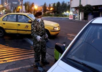 In Tehran a member of the Revolutionary Guard disinfects a car on Wednesday, to help prevent the spread of the coronavirus.