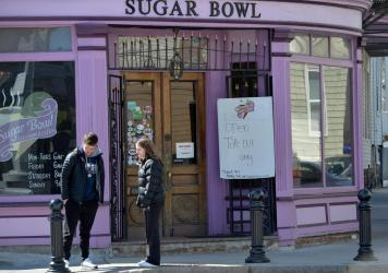 Two people wait outside the Sugar Bowl restaurant which is doing take out only during the coronavirus outbreak in Dorchester, Mass.