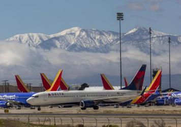 A Delta Air Lines jet taxis past Southwest Airlines jets to be parked with a growing number of jets at Southern California Logistics Airport on March 24, 2020 in Victorville, Calif. As the coronavirus pandemic grows, exponentially increasing travel restr