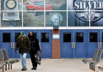 Workers leave an FCA Chrysler truck plant in Detroit on March 18 after the automaker shut down all of its North America factories as a precaution against the coronavirus.