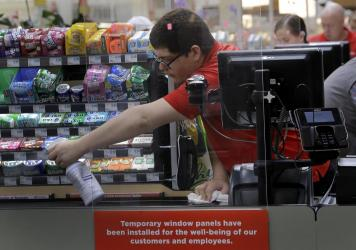 Garrett Ward sprays disinfectant behind a plexiglass panel at a Hy-Vee grocery store in Overland Park, Kan., on March 26. Stores have begun installing the shields in checkout aisles to protect clerks and help stop the spread of the coronavirus.