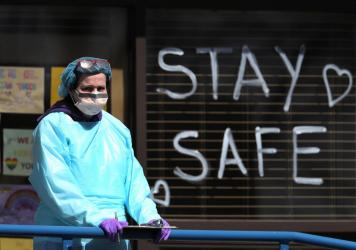 A health care worker staffs a drive-thru coronavirus testing site in Jericho, N.Y., a state that remains the hardest-hit by the COVID-19 pandemic. The disease has killed more than 10,000 people in the U.S., and 4,758 in New York.