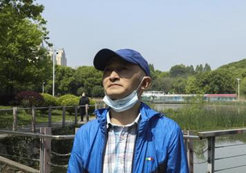 "Zhang Hai stands on a bridge where he took his father out for a walk only about four months earlier. His father died of the novel coronavirus on Feb. 1. ""The scenery is still here, but the person is gone,"" he sighs. He says he frequently comes to this pa"
