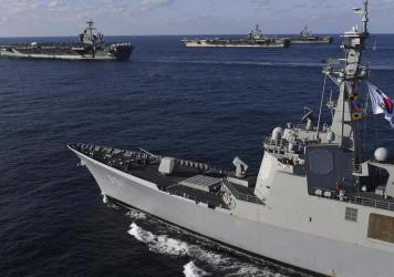 Three U.S. aircraft carriers USS Theodore Roosevelt (top left) USS Ronald Reagan (top center) and USS Nimitz (top right) participate in exercises with South Korean forces in 2017.