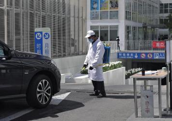 A worker wearing a protective face mask to prevent the spread of the new coronavirus sprays disinfectant as a vehicle prepares to enter an office building carpark in Beijing, on Monday.