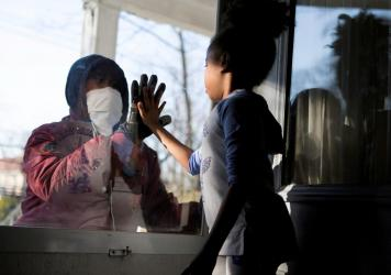 Countries under coronavirus lockdowns should only ease those restrictions if they can control new infections and trace contacts, the World Health Organization says. Here, Hashim, a health care worker, recently greeted his daughter through a glass door as
