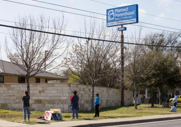 Anti-abortion rights activists pray outside a Planned Parenthood clinic that offers abortions in Austin, Texas in 2016. Planned Parenthood clinics in Colorado, New Mexico, and Nevada are reporting an influx of patients from Texas, after an order from Tex