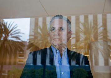 Co-founder Martin Pichinson stands for a portrait behind a lobby window at Sherwood Partners, which helps shut down startups in financial trouble. (Photo by Jessica Pons for NPR)
