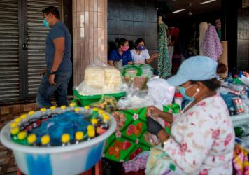 People wear face masks as a preventive measure against the spread of the new coronavirus, COVID-19 at a market in Managua, on April 16, 2020, a day after Nicaraguan President Daniel Ortega spoke of the coronavirus pandemic and announced there would be no