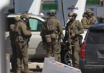 Members of the Royal Canadian Mounted Police (RCMP) tactical unit confer after the suspect in a deadly shooting rampage was killed at a gas station in Nova Scotia, Canada, on Sunday.