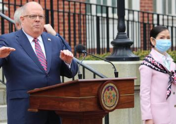 Maryland Gov. Larry Hogan speaks at a news conference on Monday in Annapolis, Md., with his wife, Yumi Hogan (right), where the governor announced Maryland has received a shipment from a South Korean company to boost the state's ability to conduct tests