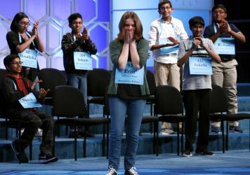 """The Scripps National Spelling Bee is canceling its 2020 national finals, citing """"uncertainty around when public gatherings will be possible or advisable."""" Here, Erin Howard, center, is cheered by her fellow co-champions during last year's finals in Oxon"""