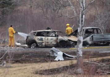 A volunteer firefighter douses hotspots near destroyed vehicles linked to the deadly weekend shooting rampage in Nova Scotia, on Monday.