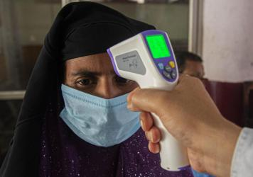 A health worker checks the temperature of passengers about to board a bus on Monday to their villages in Gauhati, India, after they were stranded during a lockdown to curb the spread of the new coronavirus.