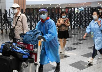 Travelers at Beijing Daxing Airport wear face masks on Thursday to avert the spread of the coronavirus.