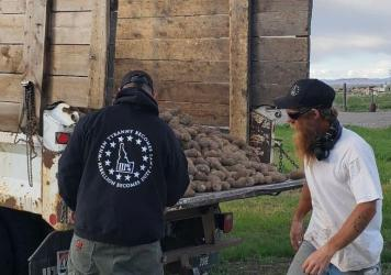 Members of the Real Idaho Three Percenters unload potatoes this week as part of a volunteer effort to give away crops that were unsold because of the coronavirus pandemic. Their activities raise questions about the role of militias in the pandemic respon
