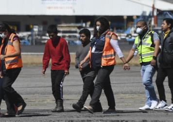 Guatemalan immigration officials use protective equipment as a preventive measure against the new coronavirus as they receive Guatemalan migrants deported from the U.S., at the Air Force base in Guatemala City on March 12.