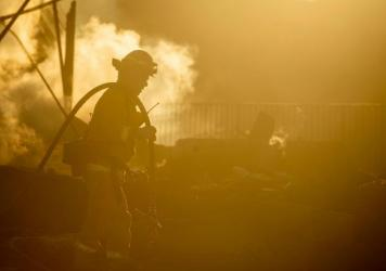A firefighter sprays down the smoldering remains of a burning home during the Hillside Fire in the North Park neighborhood of San Bernardino, Calif., on Oct. 31, 2019. Some wildland firefighters worry whether they can do their jobs safely during a global
