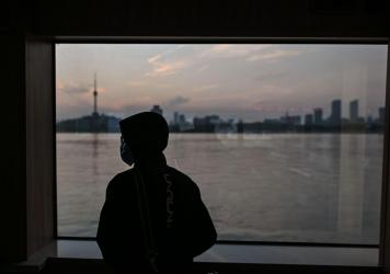 A man wearing a face mask travels on a ferry to cross the Yangtze River in Wuhan in April. Chinese officials are working to silence people suspected of challenging the narrative that authorities in Wuhan and Beijing acted swiftly and efficiently to conta