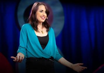 Emily Quinn speaks from the TED stage at TEDWomen 2018