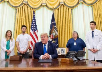 President Trump speaks about COVID-19 alongside nurses after signing a proclamation in honor of National Nurses Day in the Oval Office of the White House on Wednesday. Trump and Vice President Pence have not worn face masks during public events, which go