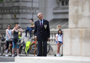 A 93-year-old veteran of World War II observes a moment of silence at the Cenotaph war memorial in London, where British residents — like much of Europe — marked a subdued 75th anniversary of V-E Day.
