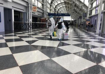A couple dressed in protective gear walks through Chicago's O'Hare International Airport last week as the normal frantic bustle in the terminal was replaced by an unsettling calm.