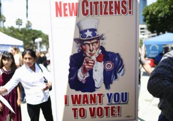 A sign encourages newly sworn-in U.S. citizens to register to vote outside a naturalization ceremony in 2019 in Los Angeles. After failing to get the now-blocked citizenship question on the 2020 census, the Trump administration is continuing to gather go