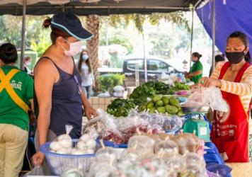"""A shopper buys vegetables last month in Vientiane, Laos. The government announced that some offices and businesses will resume normal operations on Monday. The country has confirmed 19 COVID-19 cases and no deaths.<em></em><a href=""""https://laotiantimes.c"""
