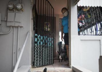 Delia Vicente peeks out of the doorway of her house in San Juan, Puerto Rico, in April. The Census Bureau says its workers on the island are getting ready to resume leaving paper forms for the 2020 census outside of front doors.