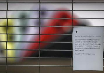 A sign on a shuttered Apple Store at the International Plaza shopping center in Tampa, Fla. The location has been closed because of the coronavirus and is scheduled to reopen Thursday.